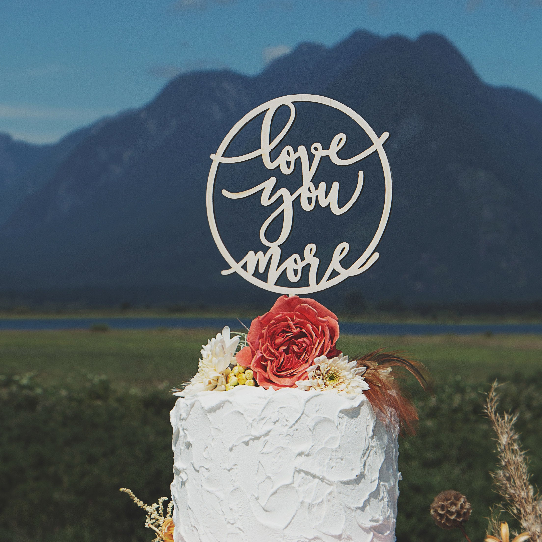 Love you more in a circle cake topper by Thistle and Lace